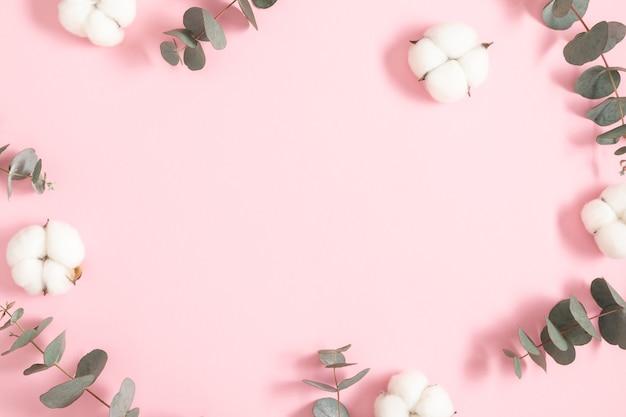 Flores de algodón y hojas de eucalipto sobre un fondo rosa pastel
