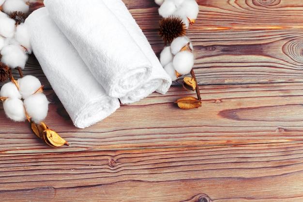 Flores de algodón con toalla en mesa de madera