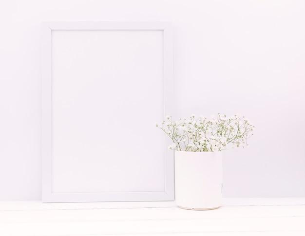 Flores de aliento del bebé en jarrón de cerámica con marco de fotos vacío