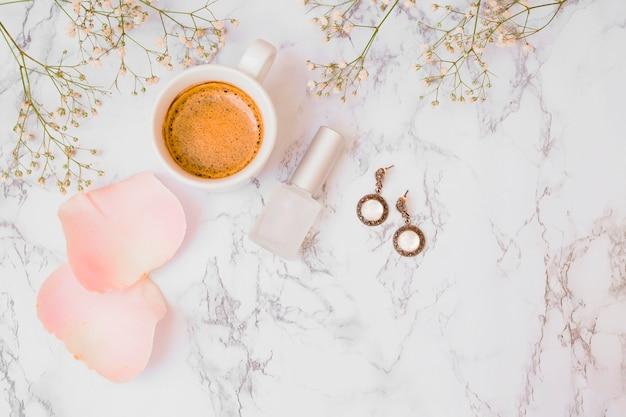 Flores de aliento de bebé con pétalos de rosa; taza de café; botella de esmalte de uñas y aretes sobre fondo texturado de mármol blanco