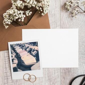 Flores de aliento de bebé en el sobre con papel en blanco; anillos de boda y marco polaroid