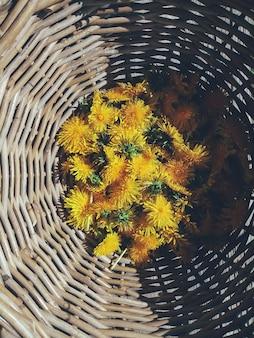 Flores amarillas del diente de león en un tazón de mimbre