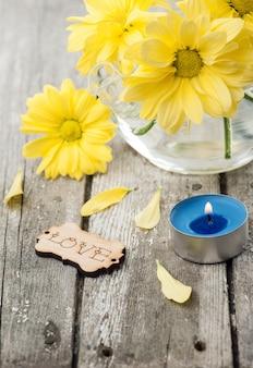 Flores amarillas frescas de la margarita, firman el amor y la vela encendida
