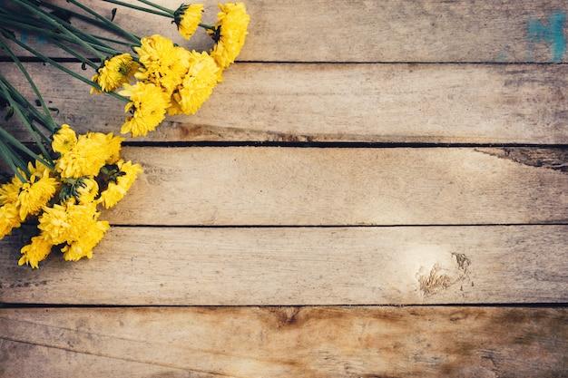 Flores amarillas de ramo, vista superior sobre textura de fondo de madera con espacio de copia