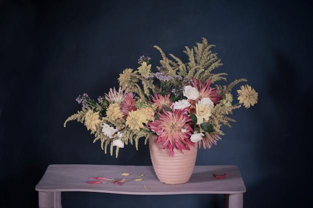 Flores amarillas y rojas en florero en estante vintage