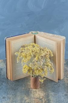 Flores amarillas secas y libro sobre mármol.