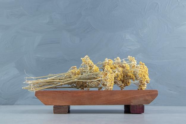 Flores amarillas secas sobre tabla de madera.