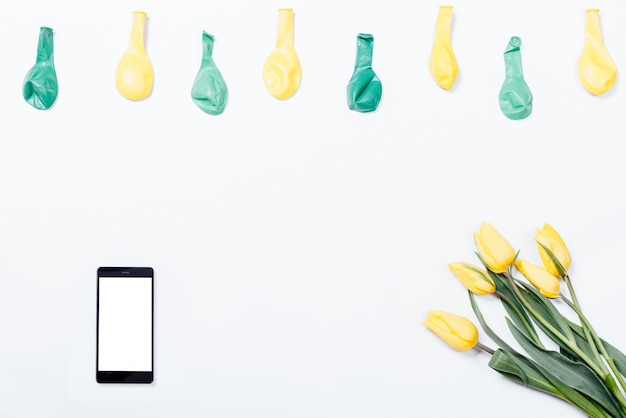 Flores amarillas, teléfono móvil y globos sobre una mesa blanca