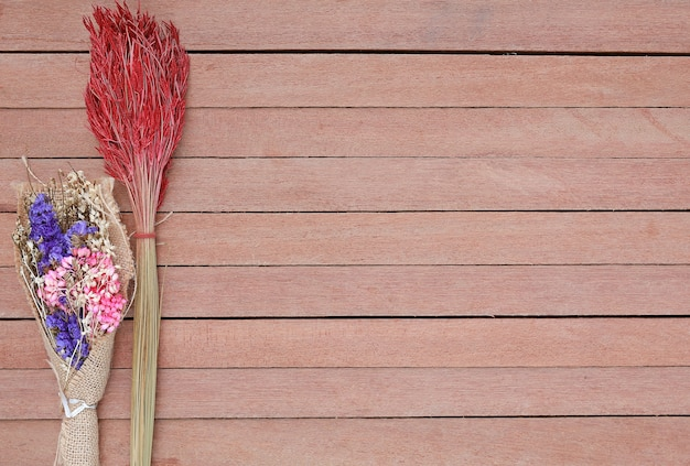 Flores de arbusto secas sobre un fondo de tablón de madera