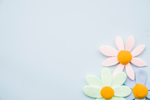Flores de arcilla pastel sobre fondo gris