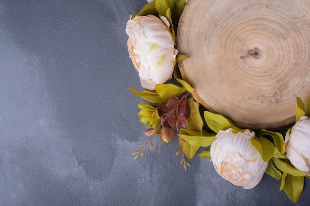 Flores artificiales alrededor de la madera en rollo en azul.