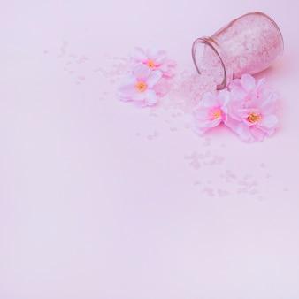 Flores artificiales y sal derramada de tarro sobre fondo rosa