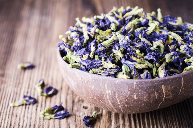 Flores azules secadas del guisante de mariposa en fondo de madera.