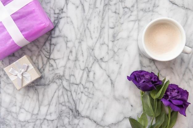 Flores azules con taza de café y regalos.