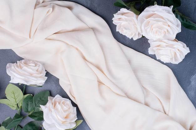 Flores blancas artificiales sobre azul con tela de satén.