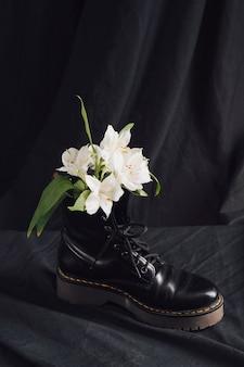 Flores blancas en bota de cuero oscuro.