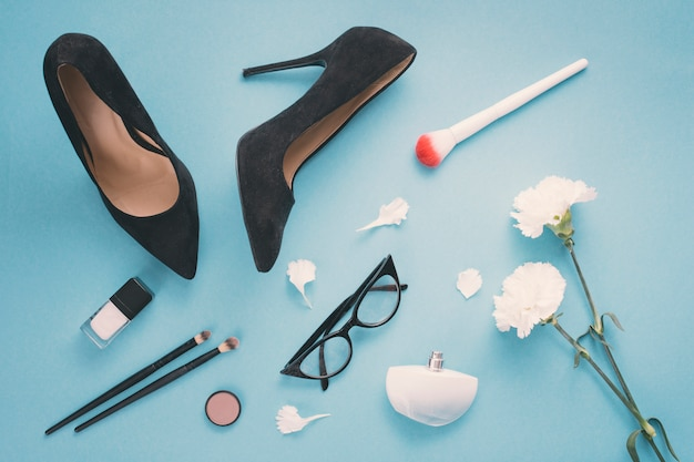 Flores blancas con cosméticos y zapatos de mujer en mesa azul.