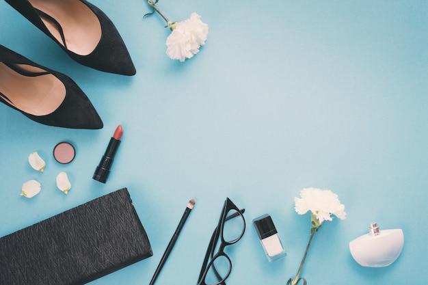 Flores blancas con cosméticos y zapatos de mujer en mesa.
