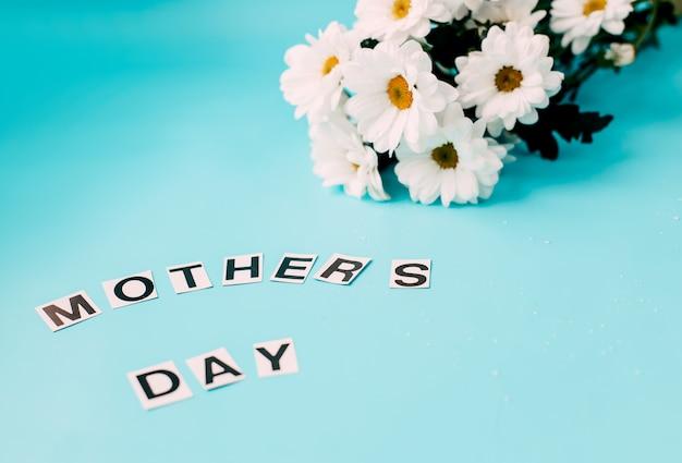 Flores blancas del día de la madre sobre fondo azul.