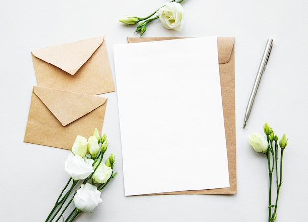 Flores blancas de eustoma, sobres y hojas de papel blanco en blanco