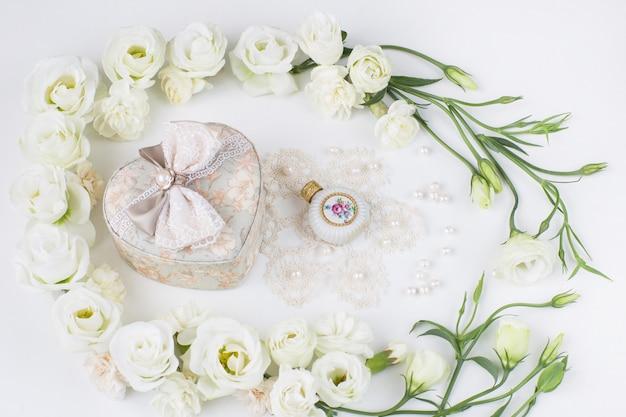 Flores blancas forradas con un joyero en forma de corazón, frasco de perfume, perlas y encaje.