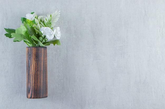 Flores blancas frescas en una jarra de madera, sobre la mesa blanca.