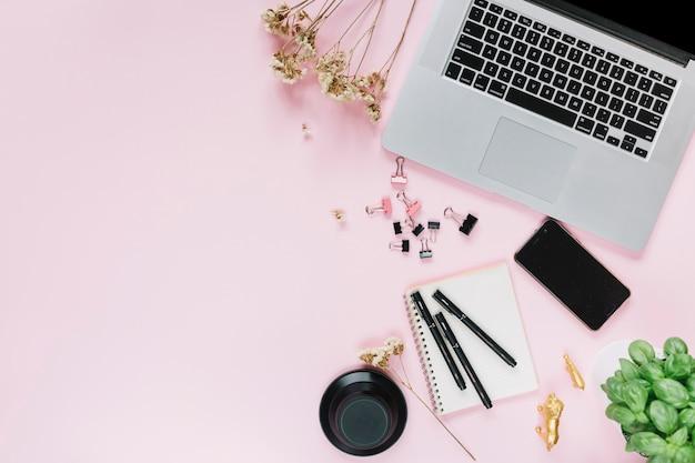 Flores blancas con laptop; teléfono inteligente y papelería sobre fondo rosa