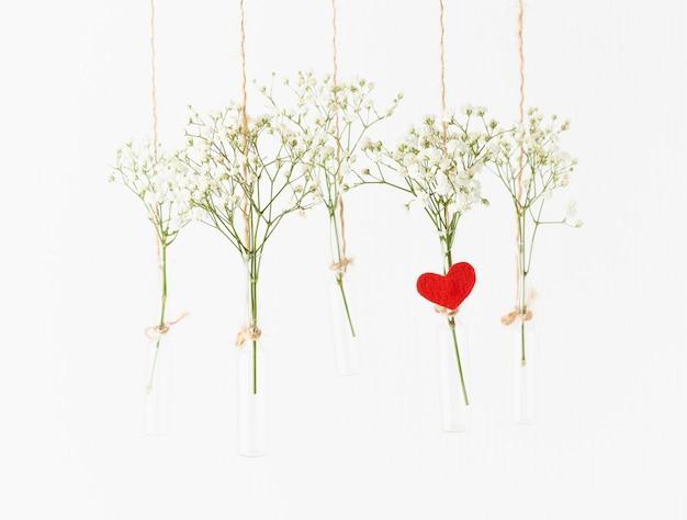 Flores blancas en mini jarrones de cristal colgando. concepto de san valentín