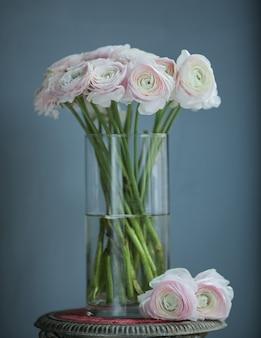 Flores blancas rosadas en la botella sobre la mesa