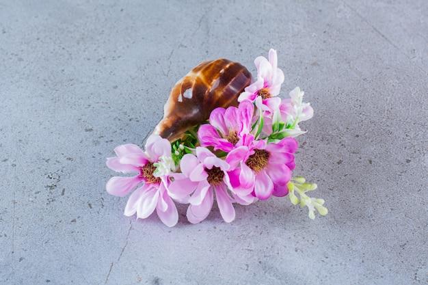 Flores blancas y rosadas con conchas marinas en gris.