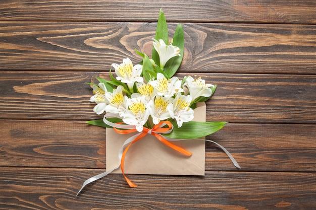 Flores blancas tiernas pequeñas orquídeas en un sobre de correo astuto sobre un fondo de madera