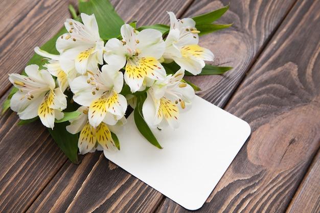 Flores blancas tiernas pequeñas orquídeas sobre un fondo de madera marrón