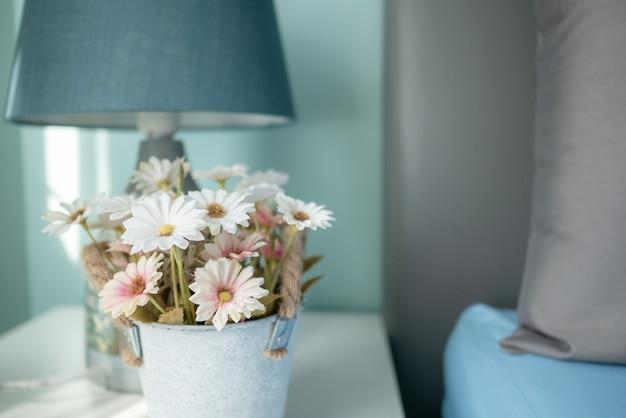 Flores borrosas y la lámpara sobre la mesa con rayos de sol en el dormitorio
