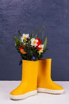 Flores En Unas Botas Amarillas Foto Gratis