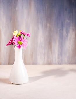 Flores brillantes en jarrón blanco sobre mesa