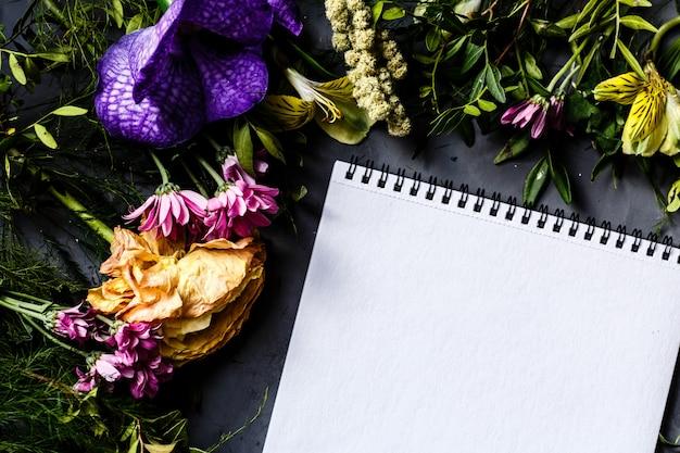 Flores brillantes en una mesa gris y un cuaderno vacío.
