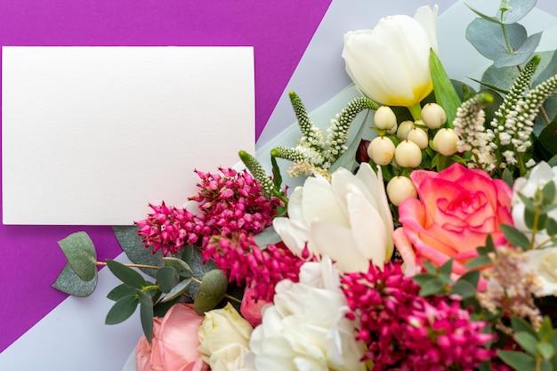 Las flores se burlan de la tarjeta de regalo. tarjeta de felicitaciones en ramo de flores de primavera sobre fondo morado.