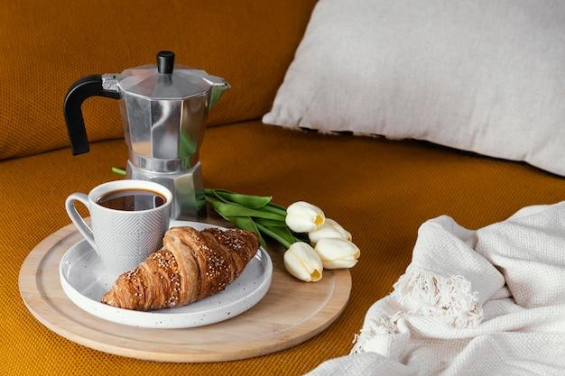 Flores, café y croissant de ángulo alto