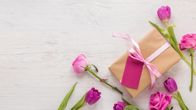 Flores con caja de regalo en mesa de luz.