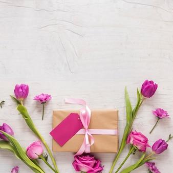 Flores con caja regalo en mesa madera.