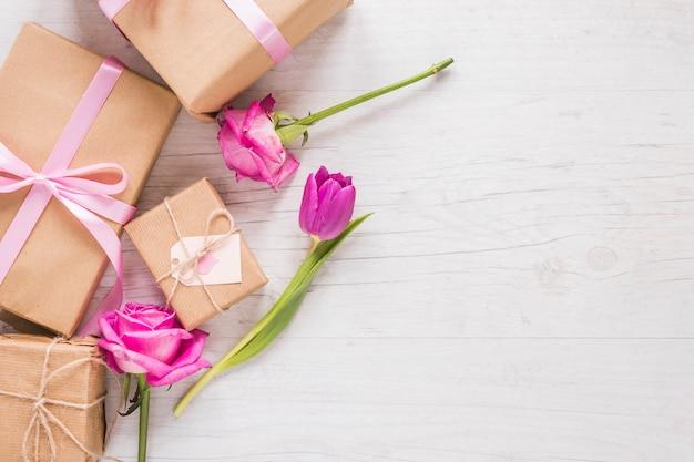 Flores con cajas de regalo en mesa.