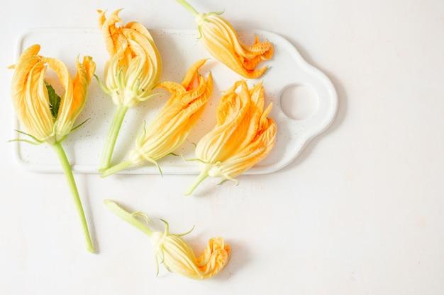 Flores de calabacín en un tablero blanco