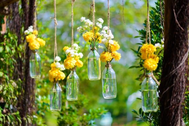 Las flores de caléndula en una botella de vidrio colgando.