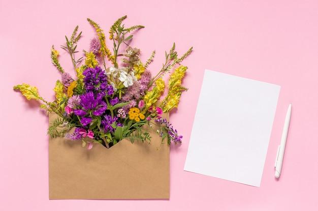 Flores de campo en sobre artesanal y tarjeta de papel blanca vacía.