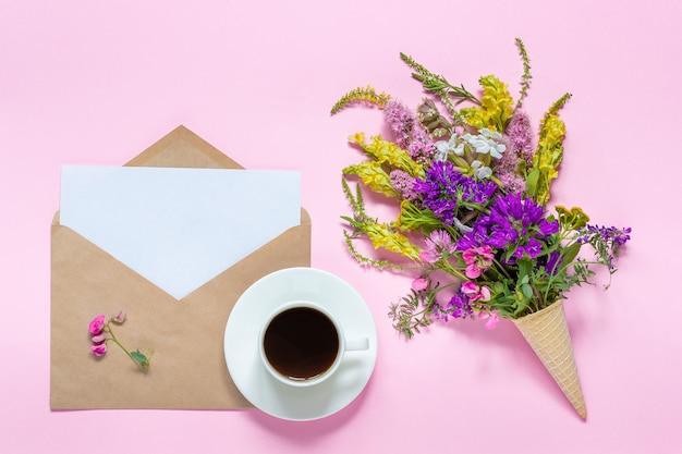Flores de campo, sobre artesanal y taza de café.