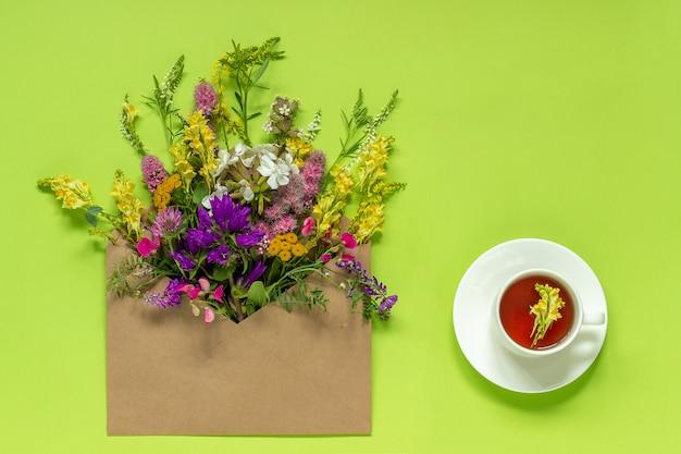Flores de campo en sobre artesanal y taza de té de hierbas.