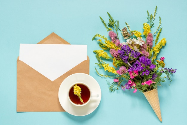 Flores de campo, sobre artesanal y taza de té de hierbas.