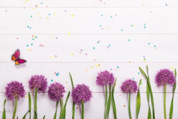 Flores de cebolla, confeti y mariposa sobre fondo de madera. hola concepto de primavera.