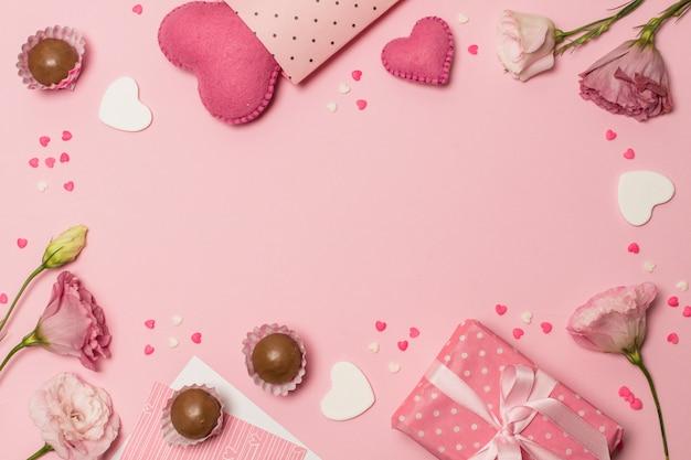 Flores cerca de corazones, caja actual y dulces de chocolate.