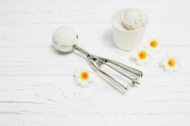 Flores cerca de primicia y taza de helado